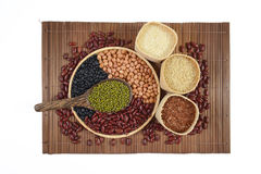 Sädes- korn och fröbönor som är användbara för hälsa i wood skedar på vit bakgrund Arkivfoton