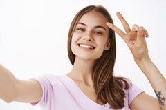 Säga hi till internetanhängare Charma vänskapsmatch-se den glade flickan med brunt hår som ler visa i huvudsak fred eller royaltyfri bild
