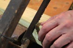 Sägen einer Holzleiste Stockfotos