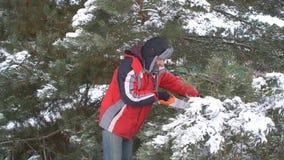 Sägende Kiefernniederlassungen des attraktiven Mannes in seinem schneebedeckten Garten des Winters für frohe Weihnachten und gute stock video