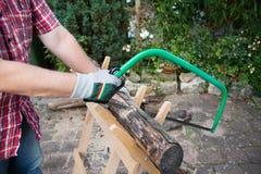 Sägendes Brennholz manuell mit einer Metallsäge auf einem hölzernen Sägebock lizenzfreie stockfotos