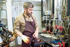 Säker ölfabriksarbetare som sätter flaskor i ask royaltyfria bilder