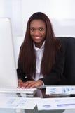 Säker affärskvinna som arbetar på skrivbordet Arkivfoto