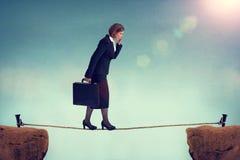 Säker affärskvinna som går en spänd lina arkivfoton