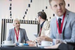 Säker affärskvinna som talar till affärsmannen i konventcentrum Arkivfoto