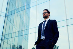 Säker affärsman i exponeringsglas som står mot kontorsbyggnad Royaltyfri Foto