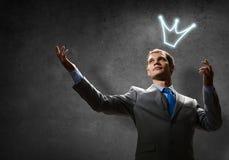 Säker affärsman i kronaanseende som isoleras på grå färger med hans korsade armar Arkivbild