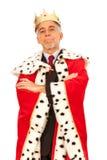 Säker affärsman i kronaanseende som isoleras på grå färger med hans korsade armar Royaltyfri Foto
