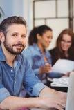 Säker affärsman som använder bärbara datorn mot kvinnliga coworkers arkivbild