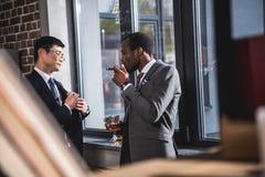 Säker affärsman som dricker alkoholdrycken och röker cigarren medan kolleganederlagpengar in i dräktfacket royaltyfri bild