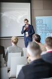 Säker affärsman som förklarar strategi till åhörare i seminariumkorridor Arkivbild