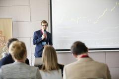 Säker affärsman som ger presentation i seminariumkorridor på konventcentret Arkivbild