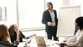Säker affärsman som ger presentation på flipchart till kollegor i styrelse stock video