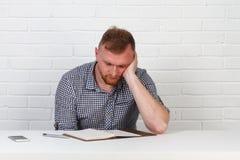 Säker affärsman som läser ett avtal Affärsman som läser ett avtal i ett kontor bak ett skrivbord isolerat sinnesrörelser Royaltyfria Foton