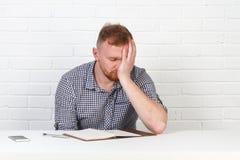 Säker affärsman som läser ett avtal Affärsman som läser ett avtal i ett kontor bak ett skrivbord isolerat sinnesrörelser Fotografering för Bildbyråer