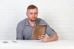 Säker affärsman som läser ett avtal Affärsman som läser ett avtal i ett kontor bak ett skrivbord isolerat sinnesrörelser Royaltyfri Foto