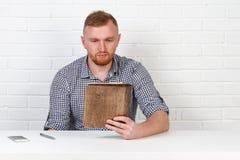 Säker affärsman som läser ett avtal Affärsman som läser ett avtal i ett kontor bak ett skrivbord isolerat sinnesrörelser Arkivbild