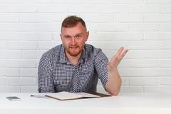 Säker affärsman som läser ett avtal Affärsman som läser ett avtal i ett kontor bak ett skrivbord isolerat sinnesrörelser Royaltyfri Fotografi
