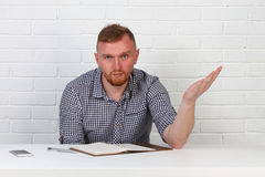 Säker affärsman som läser ett avtal Affärsman som läser ett avtal i ett kontor bak ett skrivbord isolerat sinnesrörelser Arkivfoto
