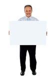 Säker affärsman som rymmer den blanka affischtavlan Royaltyfri Bild