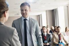 Säker affärsman som ser den offentliga högtalaren under seminarium royaltyfria foton