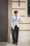 Säker affärsman som ser på hans armbandsur i dräkt fotografering för bildbyråer