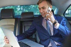 Säker affärsman som talar på mobiltelefonsammanträde i baksätet av en bil Arkivfoton