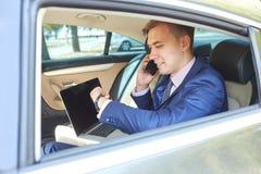 Säker affärsman som talar på mobiltelefonsammanträde i baksätet av en bil royaltyfria bilder