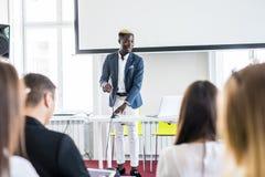 Säker Afro--amerikan affärsman som diskuterar med hans lag i en presentation affären chairs konferensskrivbordet som isoleras öve arkivfoton