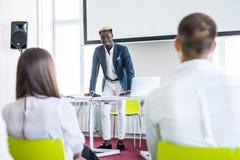 Säker Afro--amerikan affärsman som diskuterar med hans lag i en presentation affären chairs konferensskrivbordet som isoleras öve royaltyfri bild