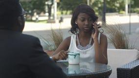 Säker afro amerikansk förvaltningschef av handeln som corporating som arbetar under den väntande på telefonen för arbetsavbrott royaltyfri fotografi