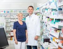 Säker apotekare And Assistant Standing in arkivbilder