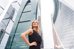Säker blond kvinna med armar som är akimbo på skyskrapabakgrund Arkivbilder