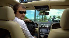 Säker chaufför i solglasögon som håller ögonen på på baksätet, höraframstickandeanvisningar Arkivfoton
