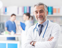 Säker doktor som poserar i kontoret Royaltyfri Foto