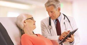 Säker doktor som talar med den äldre kvinnapatienten i kontoret royaltyfria bilder