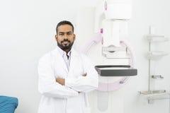 Säker doktor Standing Arms Crossed vid Mammographymaskinen Arkivbild