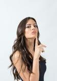 Säker förförisk lång hårskönhet med hyssjar fingergesten som ser kameran Royaltyfria Bilder
