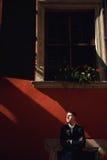 Säker gullig brudgum i en stilfull affärsdräkt, utomhus, summ Royaltyfri Bild