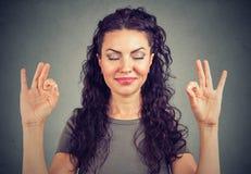 Säker gullig ung kvinna som lyckligt mediterar royaltyfri bild