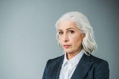 Säker hög affärskvinna i dräkt på grå färger Royaltyfri Bild