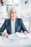 Säker hög affärskvinna som gör skrivbordsarbete på arbetsplatsen royaltyfri bild