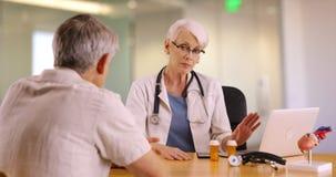 Säker hög doktor som talar med den äldre mannen i kontoret royaltyfri foto