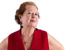 Säker hög kvinna i röda leenden på kameran Arkivfoton