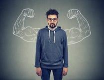 Säker hipster för stark man på väggbakgrund royaltyfria bilder