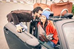 Säker hipstergrabb som har gyckel med modeflickvännen på bilen royaltyfria foton