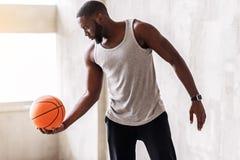 Säker idrotts- man med skägget som utför övningar med bollen Arkivfoto