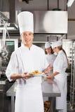 Säker kockPresenting Dish In reklamfilm Royaltyfri Fotografi