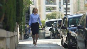 Säker kvinna som går ner gatan som ger förbipasserande hennes genomträngande kalla stirrande lager videofilmer