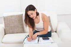 Säker kvinna som hem beräknar finanser på tabellen Royaltyfri Fotografi